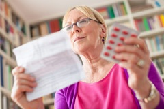 Woman reading a medicines information leaflet
