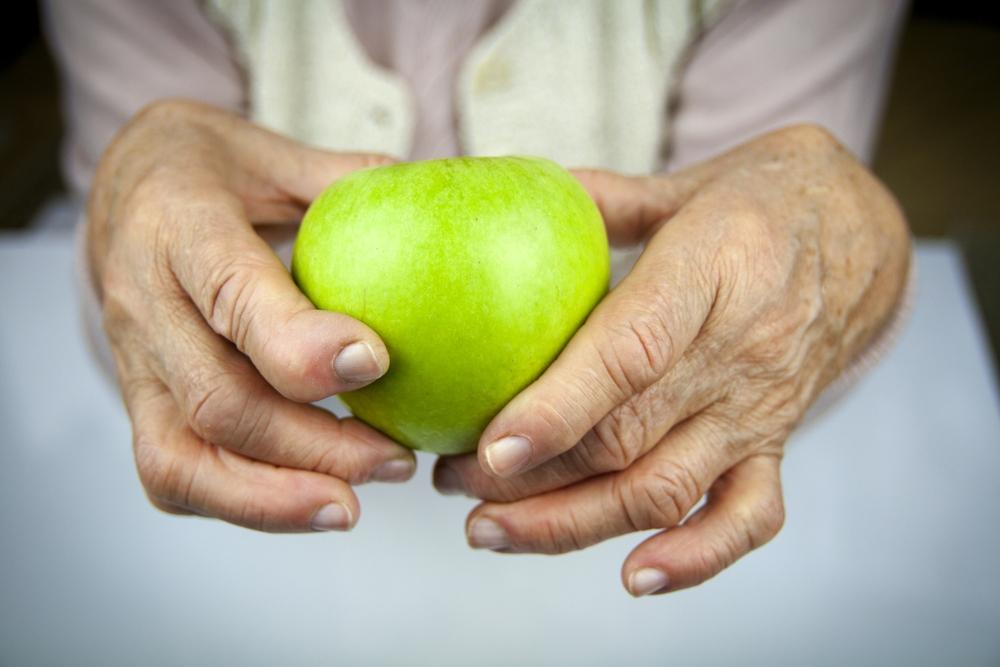 An older woman's hands, showing damage from rheumatoid arthritis, holding a green apple.